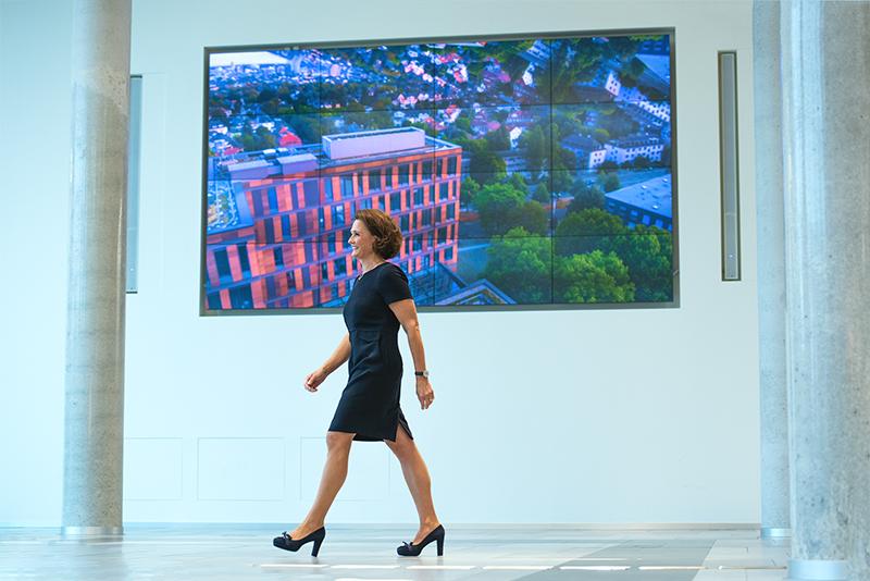 Helen Hain läuft in zügigem Schritt durch ein Foyer. Währenddessen lächelt sie sehr sympathisch und trägt ein blaues Kleid. Im Hintergrund ist ein Display zu sehen auf dem ein Gebäude abgebildet ist.