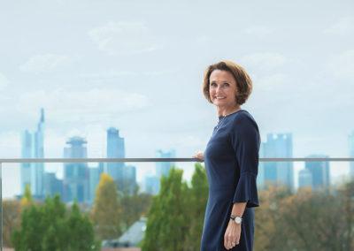 Auf dem Bild ist Helen Hain zu sehen. Sie trägt ein dunkelblaues Kleid und lächelt den Betrachter an. Im Hintergrund ist die Skyline von Frankfurt zu sehen.